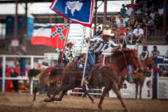 Inmates race with the state flags of Mississippi and Wyoming during the Grand Entry to the 47th annual Angola Prison Rodeo at the Louisiana State Penitentiary at Angola, LA, Sunday, October 9, 2011.
