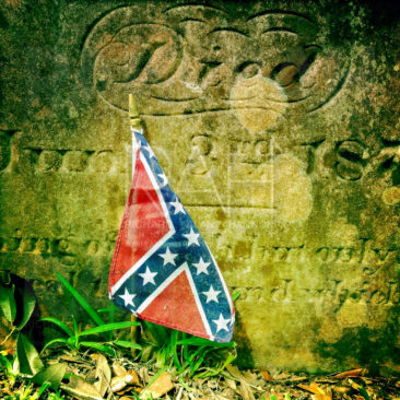 A Confederate battle flag lies against a Conferate soldier's grave at a cemetery in St. Francisville, La.  Photo by Richard Alan Hannon