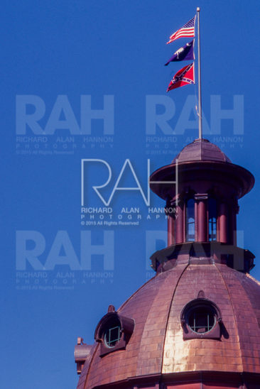 The Confederate flag flies along with the United States and South Carolina flag atop the Statehouse in Columbia, SC in 1999.  Photo by Richard Alan Hannon