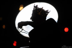 Framed by the light of a rotating search light, last year's Krewe of Orion King Norman Browning tosses beads at the start of the krewe's 11th annual Mardi Gras parade Saturday, February 6, 2010 in downtown Baton Rouge.