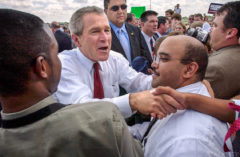 President George W. Bush reaches past Jason Wilson, Property and Development Manager with the Baton Rouge Metropolitan Airport, to shake hands on the airport tarmac following his commencement speech at LSU Friday, May 21, 2004.