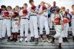 Members of the Alabama Dixie Youth Baseball team, including Kyler Colburn, 5th from left, and David Higginbothan, to Colburn's left, bow their heads in prayer during the opening ceremony of the 55th annual Dixie Youth Baseball World Series at Spartan Stadium in Gonzales Friday, August 6, 2010.