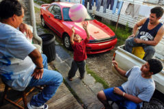 Eight-year-old Angel Reyes bounces a beach ball into the air in his driveway as his father, Melbin Soras, 43, left, and brothers Edwin, bottom, and Geovany, top right, look on in the Faubourg Marigny neighborhood of New Orleans Soras' family has been living in the same home for the past four years. They evacuated to Atlanta and then to Baton Rouge following Hurricane Katrina. Since the storm, Soras is making $15 per hour as a drywall remover, $5 more than he made in the same profession before the hurricane.