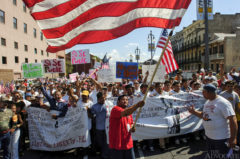 Alejandro Andrade, center, originally from Mexico City, Mexico now living in Kenner, waves a giant American flag down North Rampart Street to help lead a crowd of Latino workers rally and march during what is being called the 'National Day Without Immigrants' in New Orleans Monday.