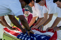 Inmate Ted Durbin watches as the American flag is removed from David Mackey's inmate-made wooden coffin. Mackey was a U.S. Army veteran and was given an inmate color guard escort and honors, minus the 21-gun salute.