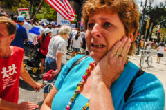 Linda Snodgress of Vero Beach, Fla. cries as she watches a crowd of Latinos march past her as she waits for a bus along St. Charles Avenue in New Orleans Monday. 'It breaks my heart for my country. You cannot come in and change the culture, the language and the law when you have entered illigally.' 'I fear for my country and this is a battle at home that every American is gonna have to wage.' 'Being a citizen has to account for something,' she said.