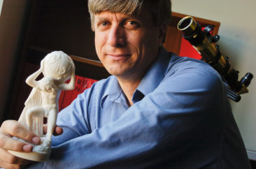 Louisiana State University astrophysics and astronomy professor Bradley E. Schaefer, Ph.D., holding a model of the Farnese Atlas, a 2nd-century Roman marble copy of a Hellenistic sculpture of Atlas.
