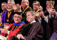 President George Bush smiles as LSU Chancellor Mark Emmert introduces him prior to giving the 2004 spring commencement speech inside the Pete Maravich Assembly Center Friday, May 21, 2004. LSU President William Jenkins is at Bush's right.