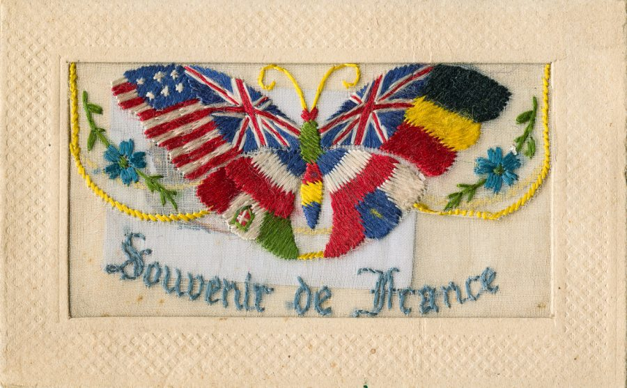 An embroidered silk postcard with the flags of the United States, the UK, France and Germany, plus the words Souvenir of France. This WWI-era postcard was given to Fern Nave from her husband, Fred Ride, a US WWI veteran.